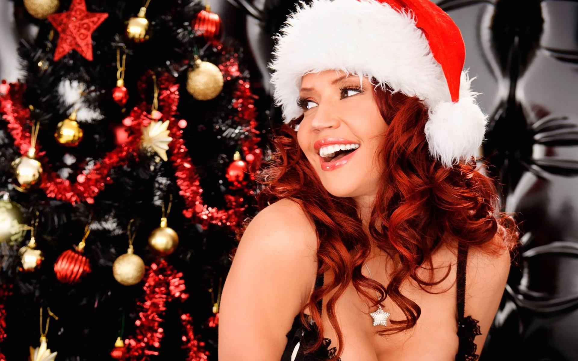 Frau mit Weihnachtsmütze vor Christbaum