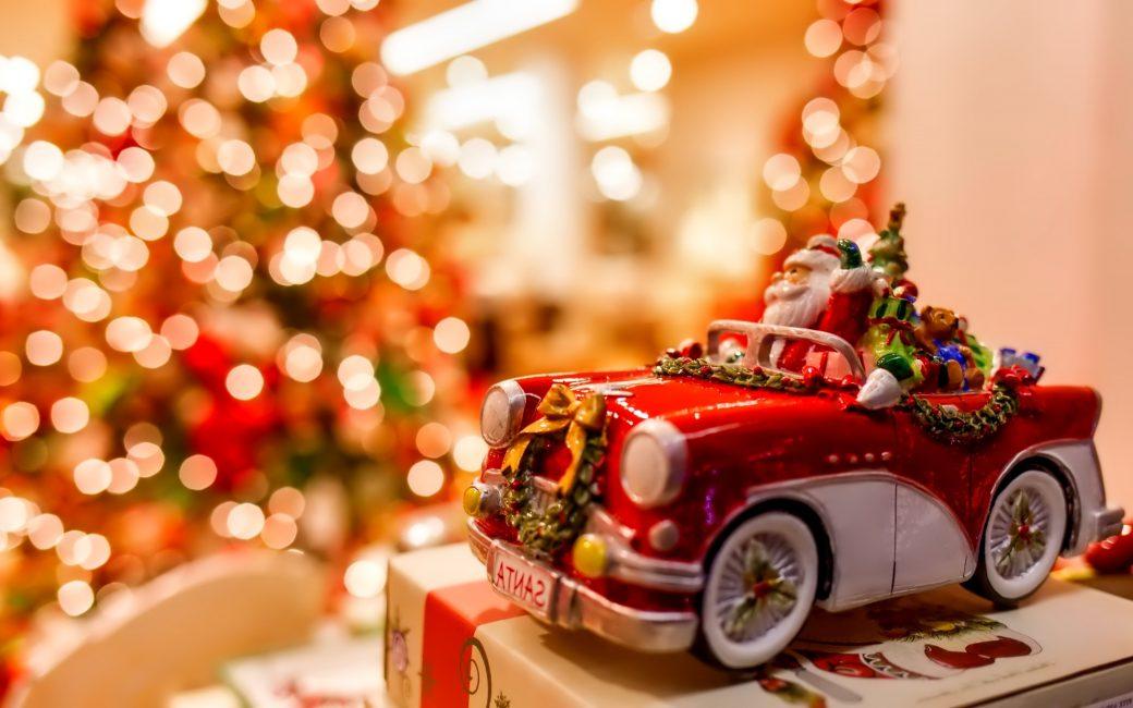 Weihnachtsmann im Spielzeug-Auto vor Christbaum