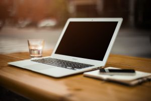 Laptop mit Notizblock und Glas Wasser